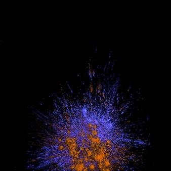 La vista dell'angolo alto dell'esplosione colorata holi porpora e arancio della polvere sopra fondo nero