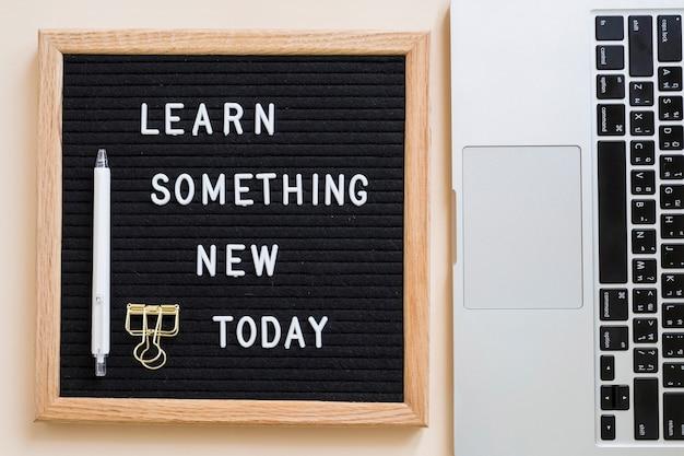 La vista dell'angolo alto di impara qualcosa di nuovo oggi il testo sull'ardesia vicino al computer portatile