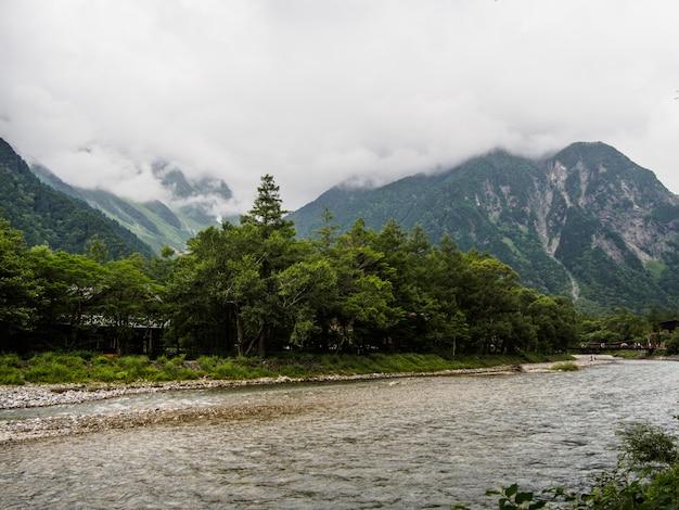 La vista della corrente scorre giù attraverso la foresta sulla montagna con il fondo della nuvola a kamikochi giappone