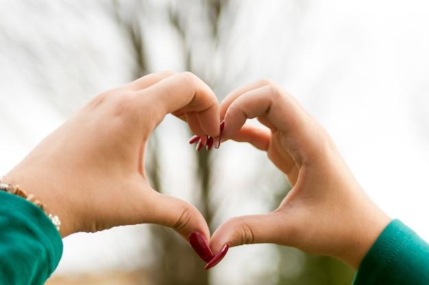 La vista della mano della donna che fa un cuore modella con le sue dita