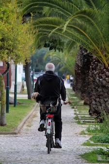 La vista di un uomo senior che cammina su una bicicletta con è cane.