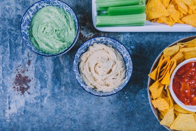 La vista elevata dei chip messicani dei nachos con guacamole e salsa sauce in ciotola