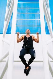La vista frontale del tipo muscolare bello sorridente che fa la tirata aumenta, portando gli abiti sportivi neri.