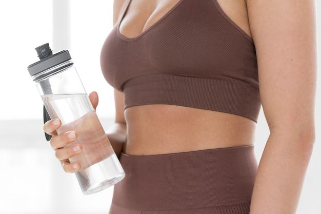 La vista frontale della donna in palestra copre con la bottiglia di acqua