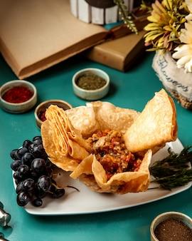 La vista laterale del caviale della melanzana è servito con lavash fritto sul piatto