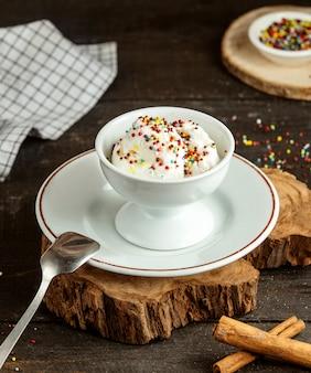 La vista laterale del gelato con spruzza in vaso bianco ceramico su di legno