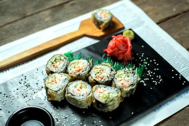 La vista laterale del maki tradizionale giapponese dei sushi della tempura dell'alimento è servito con la salsa di soia e dello zenzero sul bordo nero