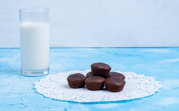 La vista laterale del muffin al cioccolato è servito con un bicchiere di latte sul blu