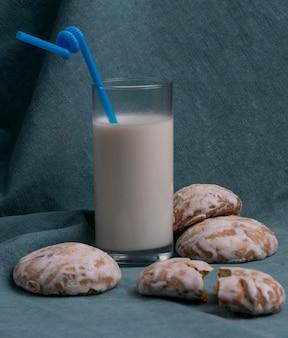 La vista laterale del pan di zenzero è servito con un bicchiere di latte sul blu