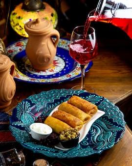 La vista laterale del pancake russo tradizionale rotola con carne e panna acida e limonata che versano in un vetro su una tavola di legno
