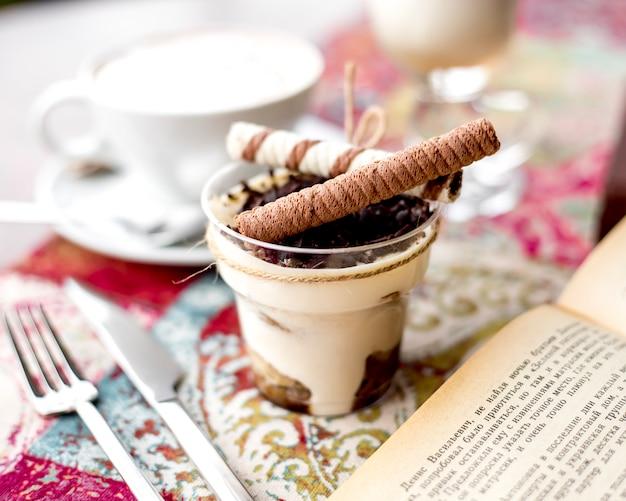 La vista laterale del tiramisù con le gocce di cioccolato e il rotolo del wafer attacca con una crema sulla tavola