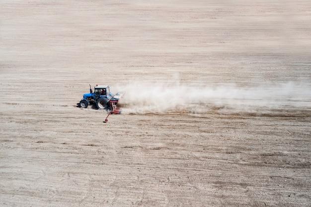 La vista laterale del trattore industriale agricolo ara il campo per la semina, vista aerea del suolo. coltivazione della terra.