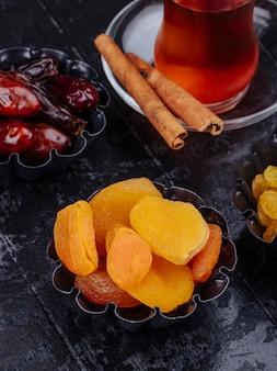 La vista laterale dell'uva passa delle albicocche secche e dei datteri secchi in mini scatole di latta servite con tè su fondo di legno nero