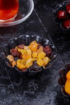 La vista laterale dell'uva passa e dei datteri secchi in mini scatole di latta servite con tè su fondo nero