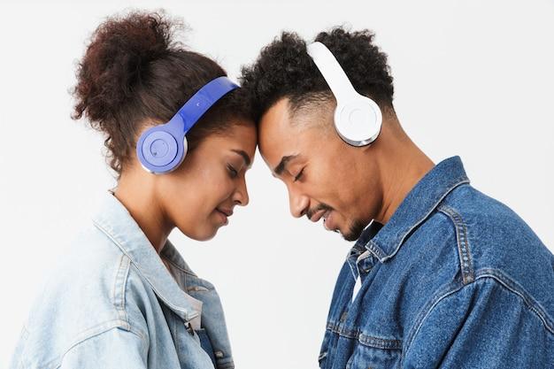 La vista laterale della coppia africana piacevole in camicie di jeans si tocca la fronte mentre ascolta la musica in cuffia con gli occhi chiusi sopra la parete grigia