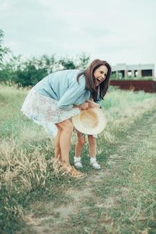 La vista laterale della giovane madre e figlia con cappelli su erba verde