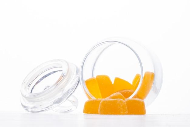 La vista laterale delle caramelle gialle della marmellata d'arancia ha sparso da un barattolo di vetro su bianco