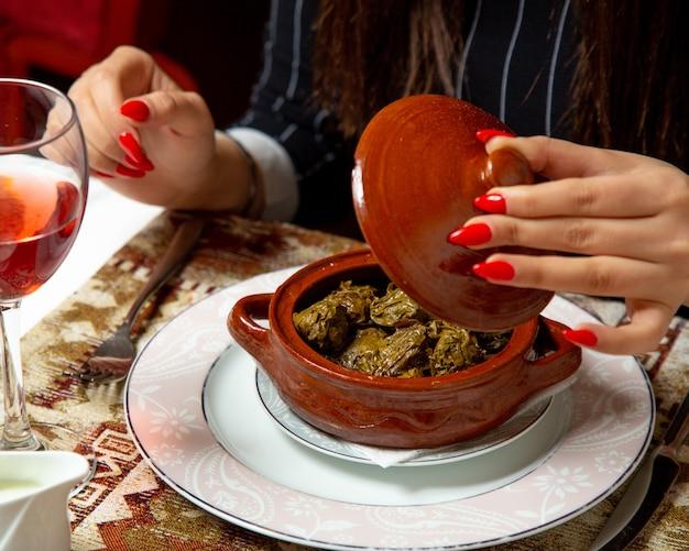 La vista laterale delle mani femminili che aprono il vaso di argilla con l'uva tradizionale lascia il dolma