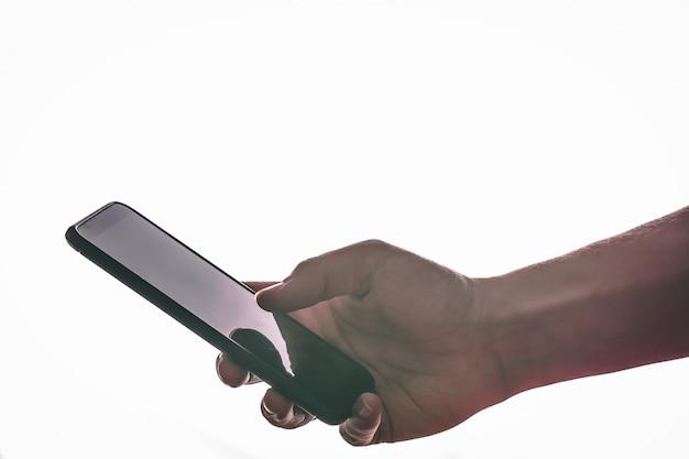 La vista laterale delle mani sta toccando lo schermo contro un bianco.