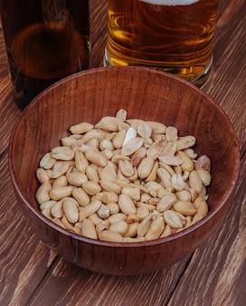 La vista laterale dello spuntino della birra ha salato le arachidi in una ciotola di legno con la tazza di birra su rustico