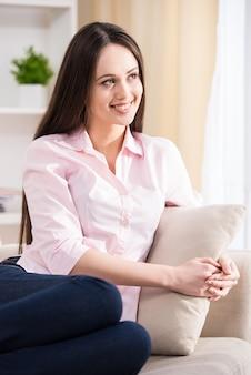 La vista laterale di bella donna sta collocando sul sofà.