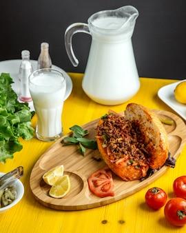 La vista laterale di carne tritata con le verdure in pane è servito con i pomodori e il limone freschi sul bordo di legno