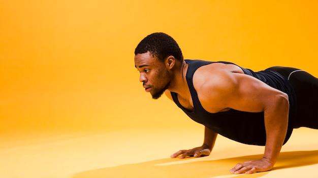 La vista laterale di fare atletico dell'uomo spinge verso l'alto con lo spazio della copia