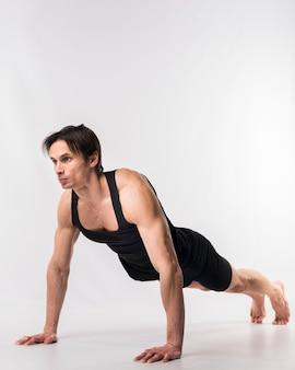 La vista laterale di fare atletico dell'uomo spinge verso l'alto