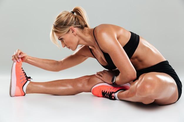 La vista laterale di una donna atleta muscolare che fa l'allungamento si esercita