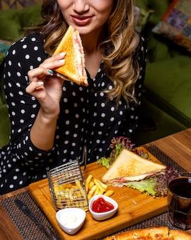 La vista laterale di una donna che mangia il panino di club è servito con le patate fritte e il ketchup alla tavola