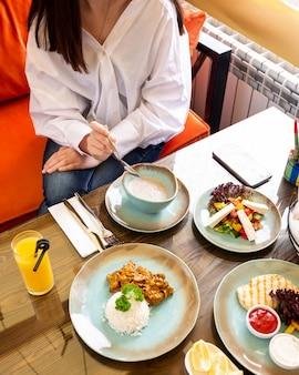 La vista laterale di una donna che si siede al tavolo è servita con vari piatti come yogurt acido con riso alle erbe con verdure e insalata