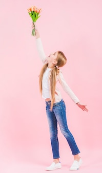 La vista laterale di una ragazza che alza la sua mano che tiene il tulipano fiorisce a disposizione che sta contro il fondo rosa