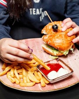 La vista laterale di una ragazza che mangia l'hamburger di pollo è servito con le patate fritte e le salse alla tavola