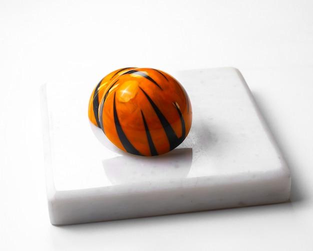 La vista laterale ha decorato la caramella di cioccolato di coloritura della tigre sul supporto bianco