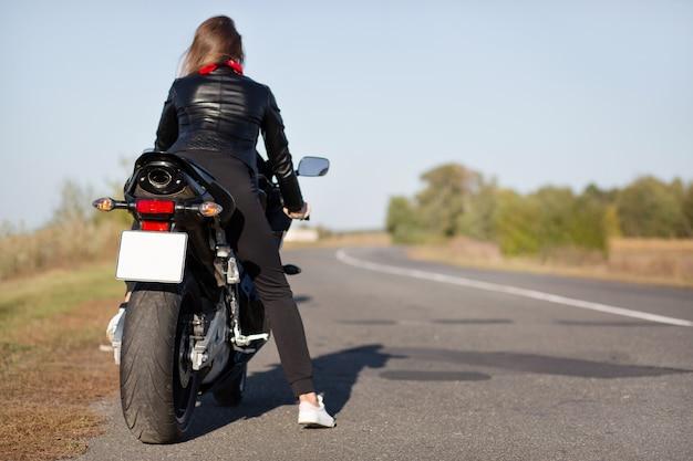 La vista posteriore dell'elegante motociclista in moto, copre la lunga destinazione, cavalca in campagna in strada aperta, gode del tempo per rilassarsi