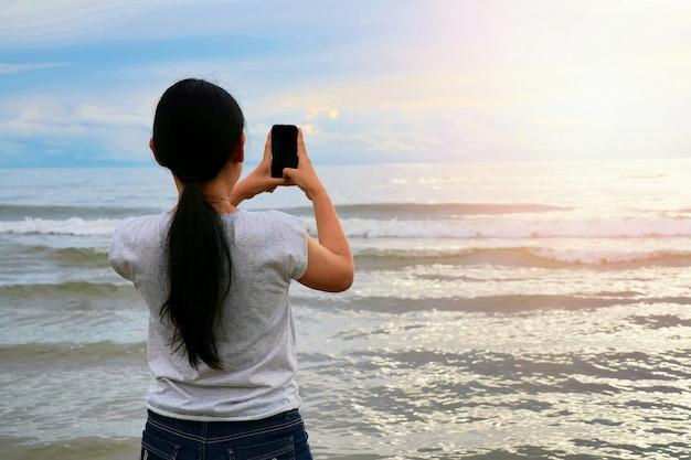 La vista posteriore della donna asiatica dei capelli lunghi prende una foto dal telefono cellulare con il mare, l'onda e il col