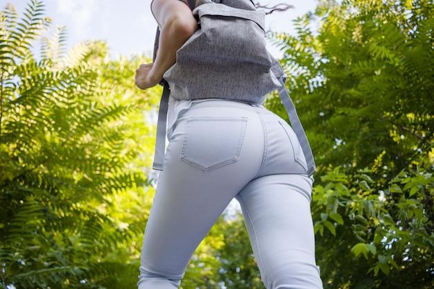 La vista posteriore della donna esile in jeans con uno zaino cammina fra gli alberi verdi di estate