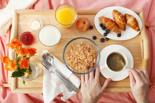 La vista sopraelevata della prima colazione è servita a letto sul vassoio di legno