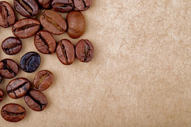 La vista superiore dei chicchi di caffè arrostiti ha isolato il fondo di struttura della carta marrone con lo spazio della copia
