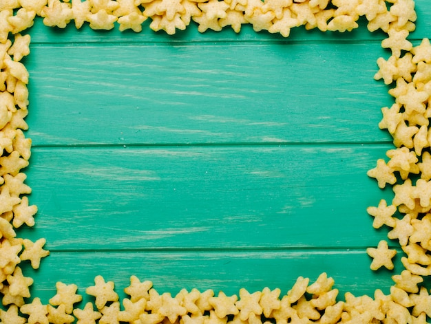 La vista superiore dei fiocchi di mais a forma di stella ha sistemato come una struttura con lo spazio della copia su fondo di legno verde