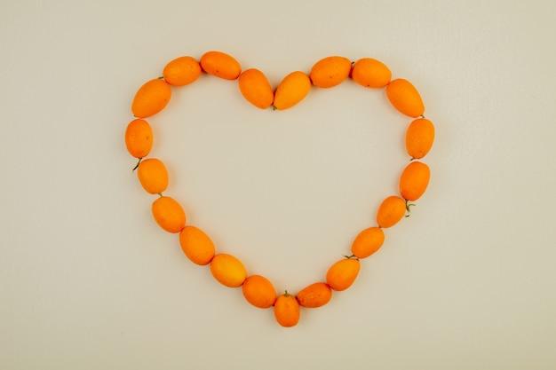 La vista superiore dei frutti maturi freschi del kumquat ha sistemato a forma di cuore su bianco