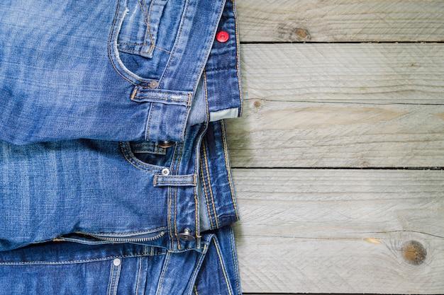 La vista superiore dei jeans blu del denim ha sistemato su di legno. concetto di abbigliamento di bellezza e moda