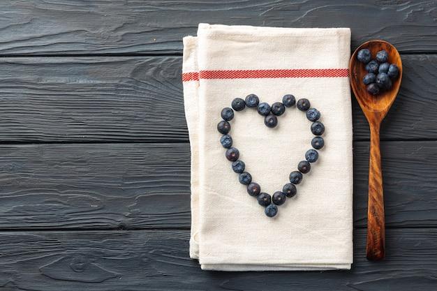La vista superiore dei mirtilli freschi ha modellato nel cuore sul tovagliolo di cotone