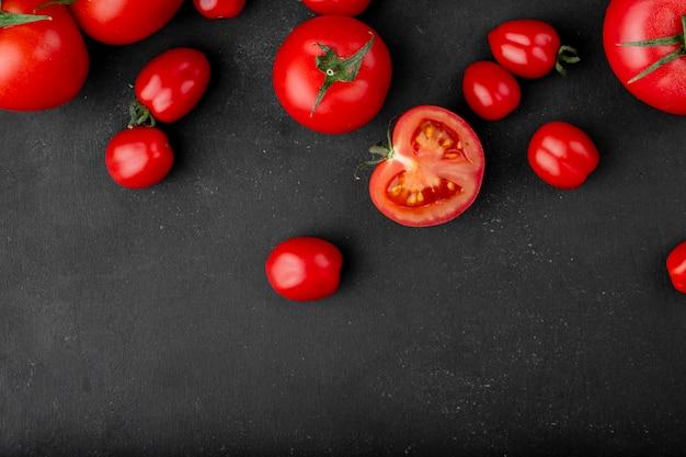 La vista superiore dei pomodori maturi freschi ha sparso su fondo nero con lo spazio della copia