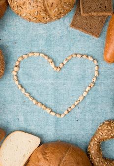 La vista superiore dei semi ha messo nella forma del cuore su fondo blu con lo spazio della copia