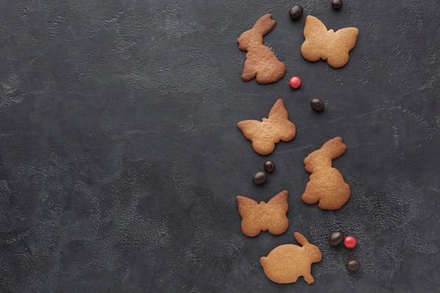 La vista superiore del coniglietto ha modellato i biscotti per pasqua con lo spazio della copia e della caramella