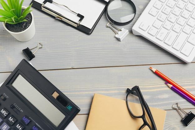 La vista superiore del desktop di legno con i vetri e gli oggetti della cancelleria si chiudono su. modello