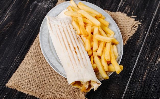 La vista superiore del doner di pollo avvolta nel lavash è servito con le patate fritte su un piatto su tela di sacco su fondo rustico