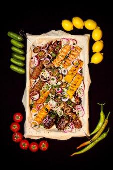 La vista superiore del kebab misto è servito con gli ortaggi freschi sul nero