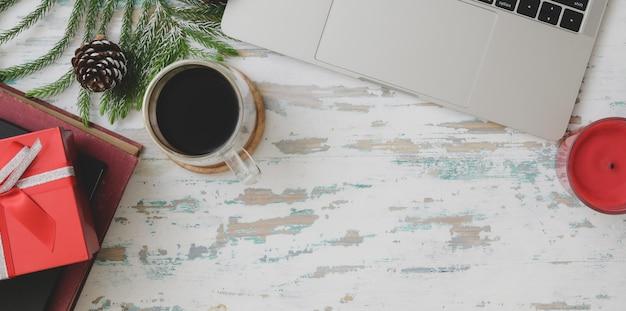 La vista superiore del natale ha decorato il posto di lavoro con il computer portatile, la tazza di caffè e il presente sullo scrittorio di legno d'annata